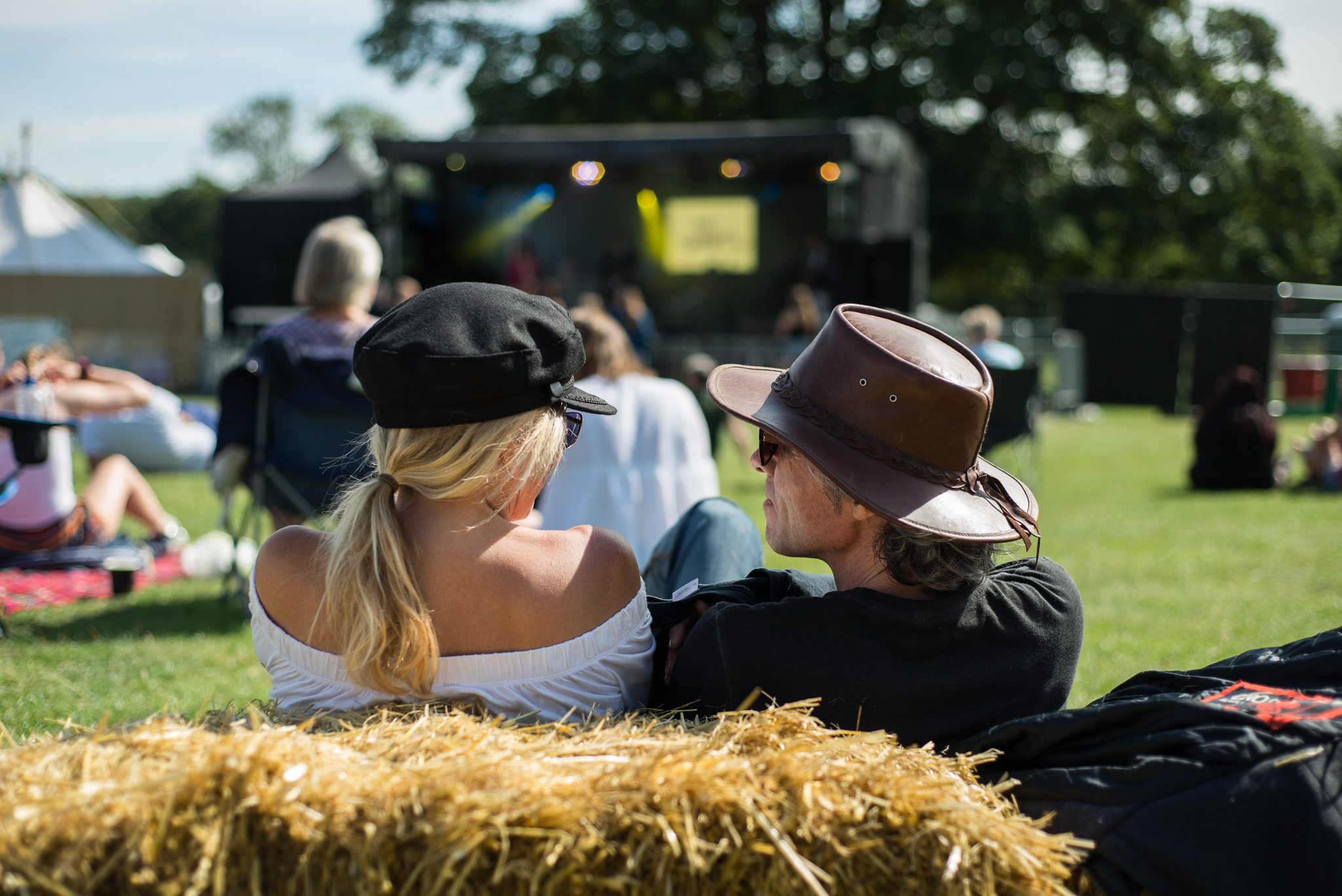 Festivalgoers sitting on a straw bale